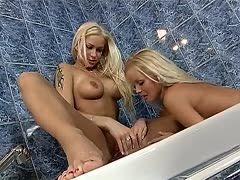 Lesbische Sexbomben spielen in der Badewanne mit Dildo